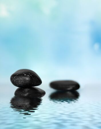 Two black massage stones in blue water background