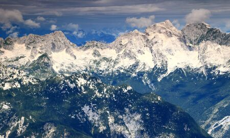 Dark green pine forested ridges over Trenta Valley with mighty Jalovec and Mangart peaks, Julian Alps, Triglav National Park, Slovenia, with Italy in clouds in the background