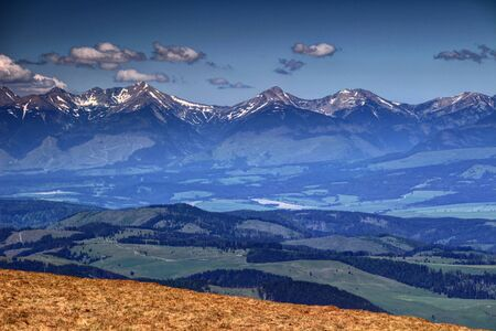 and hiking path: Snowy peaks and saddles of Western Tatras and green hills of Vah valley in Liptov region, in a sunny spring day, Slovakia, Europe