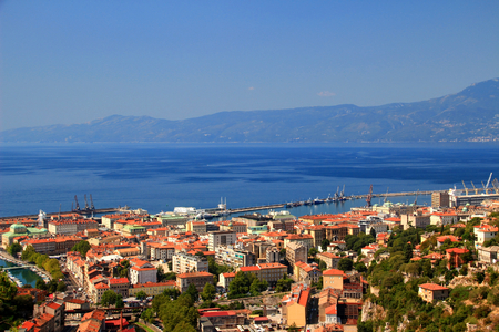 Sunny cityscape of Rijeka, the largest port of Croatia, with red rooftops of city center and the blue water of Kvarner Gulf, Adriatic Sea, in the background Ucka range, Istrian peninsula