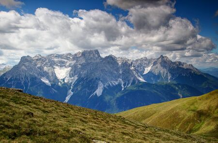 Green slopes of Carnic Alps main ridge and jagged Dreischusterspitze  Punta dei Tre Scarperi and Haunold  Rocca dei Baranci peaks in Sexten Dolomites, South Tyrol, Italy, Europe