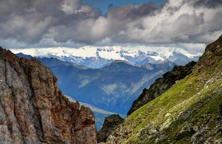Rock faces of Rosskopf, steep grassy slopes of Pfannspitze in Obstanser See, Carnic Alps, with ridges of Villgraten Mountains and glaciers of Grossglockner, Glockner Group, East Tyrol, Austria, Europe Stock Photo