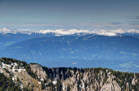 Drau  Drava valley with snow-capped Rosennock, Gerlitzen and other rounded peaks and mild slopes in Nockberge, Gurktal Alps, behind rock faces and pine trees of Karawanken range, Austria, Europe Stock Photo