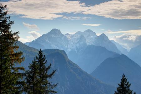 눈 덮인 Triglav 피크, 날카로운 Rjavina와 Cmir 봉우리, 소나무, Triglav 국립 공원, 줄리안 알프스, 슬로베니아, 유럽 뒤에 녹색 숲이 우거진 슬로프와 계곡이