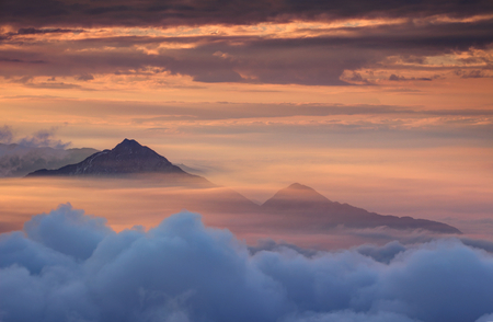 atmospheric phenomena: Two conical mountains above autumn morning mist and clouds illuminated with red color light by the rising sun, Storzic and Tolsti vrh peaks, Kamnik Savinja Alps, Gorenjska, Carniola, Slovenia, Europe Stock Photo
