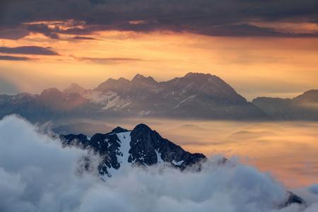 Sharp ridges of Karavanke and Kamnik Savinja Alps tower above sea of clouds and morning mist illuminated by rising red sun, Begunjscica, Grintovec, Jezerska Kocna and Skuta peaks, Gorenjska, Slovenia Stock Photo