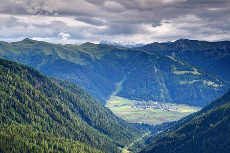 Obertilliach village in Lesachtal valley with Golzentipp ski resort in Gailtal Alps, and snowy Prijakt peak, Schober group, Hohe Tauern