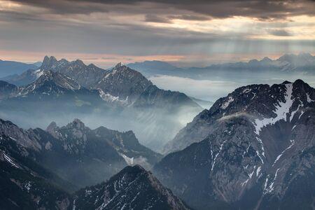 太陽光線を照らす秋の朝の霧とカラワンケン カラヴァンケ山と Loibl Ljubelj 近くカムニーク アルプスの Koschuta Kosuta と Begunjscica の尾根のギザギザを渡すと、オーストリア/スロベニアの国境 写真素材 - 89764508