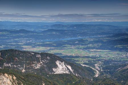 Carinthia landscape in Austria with Woerthersee, Drau river, forested hills and snowy mountains in Ossiacher Tauern, Gurktaler Alpen and Seetaler  Lavanttaler Alpen from Karawanken Karavanke range Stock Photo