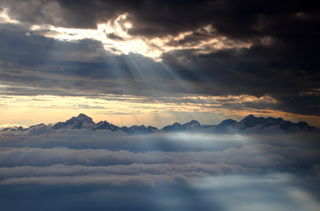 Jagged Julian Alps range with Triglav and Skrlatica, highest peaks of Slovenia, towers above sea of clouds lit by glowing light of sun rays at autumn sunset, Triglav National Park, Slovenia Europe