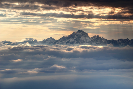 Jagged snowy peaks of Julian Alps range and Triglav, highest mountain of Slovenia, towering dramatically above glowing sea of clouds lit by sun rays light at autumn sunset Triglav National Park Europe