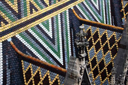 Closeup of triangle pattern multi colored glazed tiles and carved pinnacles on the steep roof of medieval St. Stephens Cathedral landmark tourist attraction of Vienna capital city of Austria Europe Stock Photo