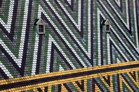 Closeup of triangle pattern multi colored glazed tiles with two windows on the steep pitch roof of medieval St. Stephens Cathedral landmark tourist attraction of Vienna capital city of Austria Europe