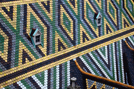 Closeup of rhombus and triangle pattern colored glazed tiles and pair of windows on steep sloping roof of medieval St. Stephens Cathedral famous tourist spot of Vienna capital city of Austria Europe