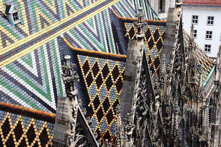 Triangle pattern multi colored glazed tiles and carved pinnacles and reliefs over side aisle of medieval Gothic St. Stephens Cathedral landmark tourist spot of Vienna capital city of Austria Europe