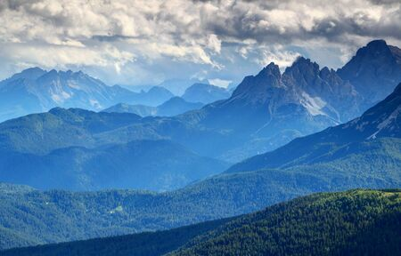 Glowing blue mist and low dark storm clouds above sunlit green conifer forests, limestone ridges and jagged sharp Monte Ciastelin peak, Marmarole mountain group Dolomiti Veneto Belluno Italy Europe