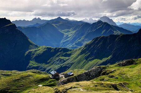 Standschutzenhutte mountain hut and lush green slopes in summer morning sunlight in Filmoor, Carnic Alps main ridge Osttirol in background jagged sharp Coglians, Peralba peaks on Austria Italy border