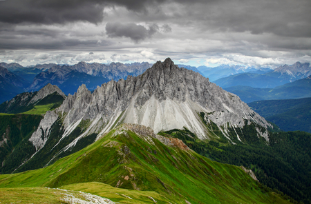 Oddly shaped sharp Crode dei Longerin peak, green hills in Carnic Alps with rocky Dolomiti Friulane ridges, Piave valley in blue mist and Dolomites in background, Belluno Veneto Northern Italy Europe Stock Photo