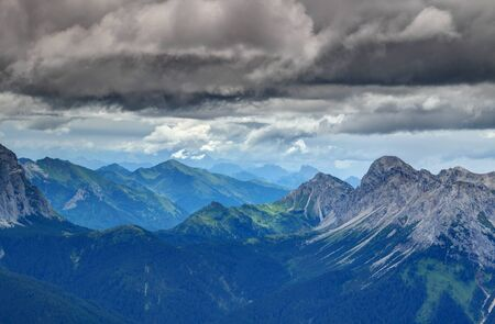 Forests, ridges and rocky limestone peaks under dramatic dark storm clouds in Rinaldo mountain group Carnic Alps with Julian Alps in background, Veneto and Friuli Venezia Giulia regions Italy Europe