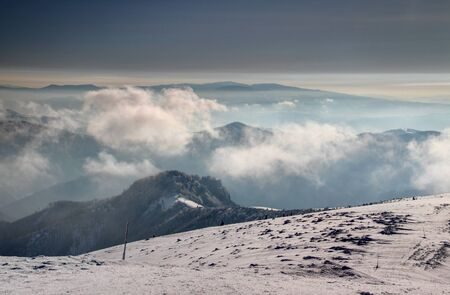Snow formations and waymarking wooden sticks between Krizna and Majerova skala peaks of Velka Fatra with fluffy low clouds, Polana and Ore Mountains in misty morning light, Carpathians Slovakia Europe