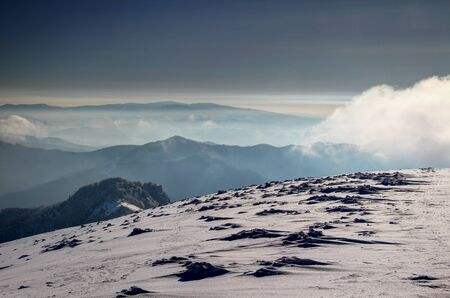 Snow formations on barren windy ridge of Krizna and Majerova skala peaks in Velka Fatra with Polana Mountains, glowing mist and low white clouds in winter morning light, Carpathians Slovakia Europe