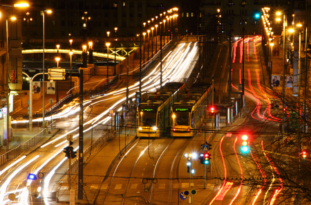BUDAPEST  HUNGARY - DEC 29 2017: Long exposure view of busy multilane Margit Boulevard and Margaret Bridge with Combino trams on line 4 6 and white red light streaks of heavy traffic of capital city Editorial