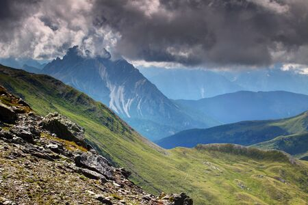 Sharp edged jagged Crode dei Longerin peak in blue mist and low level gray clouds with sunny grassy green slopes in summer, Alpi Carniche main ridge, Val Comelico Belluno Veneto Northern Italy Europe