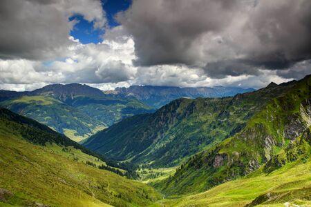 Sunny alpine meadows and forests in valleys of Karnische Alpen with ridges of Gailtaler Alpen  Lienzer Dolomiten in white cumulus clouds in background, Untertilliach Lesachtal Osttirol Austria Europe