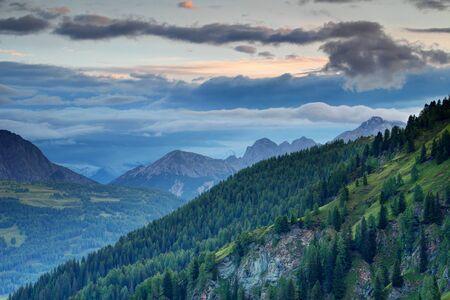 Lush dark green pine forests of Karnische Alpen and gray blue cloud stripes in calm twilight light with jagged Gailtaler Alpen Lienzer Dolomiten peaks, Untertilliach Lesachtal Osttirol Austria Europe
