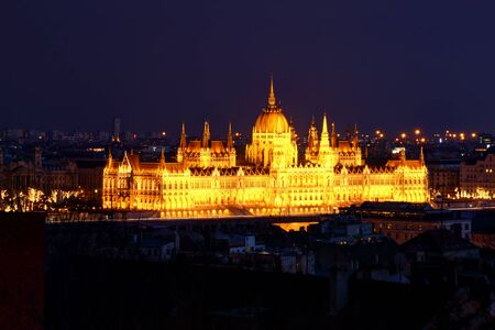 Panorama of Neo-Gothic Orszaghaz Parliament Building Hungarian legislative body seat at dusk illuminated by glowing yellow light on Danube riverbank Kossuth Square Pest Budapest Hungary Central Europe