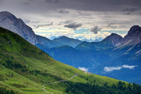 アルピ・ジュリエを背景にアルピ・ジュリエの土道とシャレーを背景にした草原の緩やかな斜面、モンテ・ペラルバ、クロスティス、キアディン、ラストローニ山頂、カドーレ・カルニア・ベルノ・ヴェネト北イタリアヨーロッパ 写真素材 - 97954893