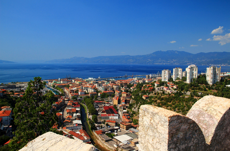 Wide angle panorama of sunny Rijeka with red rooftops of city center, high-rise buildings on green hills, blue water of Kvarner Gulf Adriatic Sea and Istrian mountains from Trsat hill Croatia Europe Stok Fotoğraf