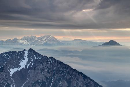 Sun rays burst through dark grey cloudy sky over rocky ridges of Karavanke and Kamnisko Savinjske Alpe ranges in haze, Begunjscica Grintovec Storzic peaks Gorenjska Kranjska Carniola Slovenia Europe