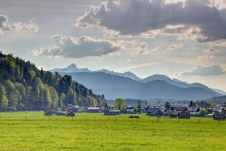Country scenery of houses and pastures in Garmisch Partenkirchen with pointed snowy Daniel peak of Ammergauer Alpen range, Bavarian Alps Northern Limestone Alps Bayern Germany Tirol Austria Europe Redakční