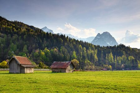 German rural scene of old timber hay barns in sunny meadow in springtime with jagged Alpspitze Waxenstein Zugspitze peaks, Northern Limestone Alps European Alps Garmisch Partenkirchen Bavaria Germany Redakční