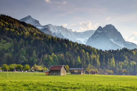 Old timber hay barns in sunny pasture in German country in springtime with snowy Alpspitze Waxenstein Zugspitze peaks, Wetterstein Northern Limestone Alps Garmisch Partenkirchen Bavaria Germany Europe