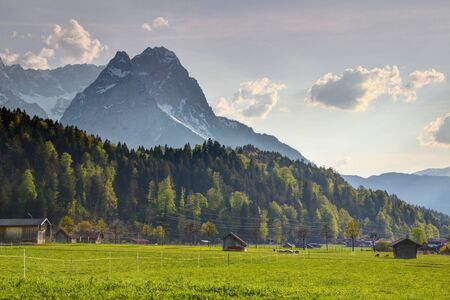 Sharp Waxenstein and Zugspitze peaks towering above trees and small wooden barns in sunny pasture, Wetterstein range Bavarian Alps Northern Limestone Alps Garmisch Partenkirchen Bayern Germany Europe