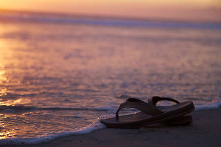 Sandals Near Water on a Beach Sunset photo