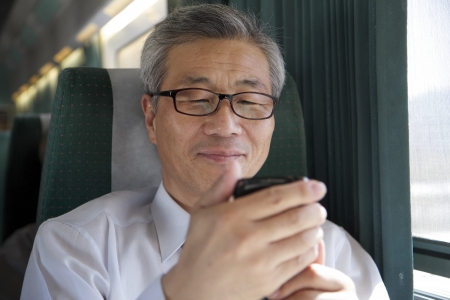 asian travel: Asian Man Riding Train Looking at Mobile Phone Stock Photo