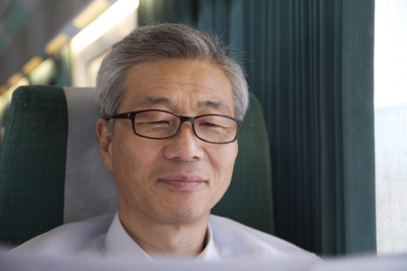 Asian Man Riding Train Reading Newspaper photo