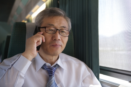 Asian Man Riding Train Talking on Mobile Phone photo