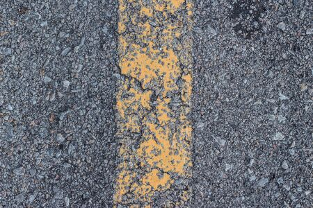 yellow line: Yellow paint line on the road against asphalt background.