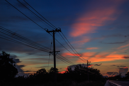 telegrama: silhouette of electric post and wires in the background of twilight sky.