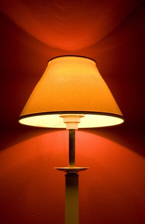 an isolated lamp with a red wall for the background