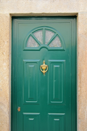 A green door with glass and a stone frame photo