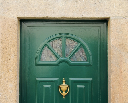 A green door with glass and a stone frame