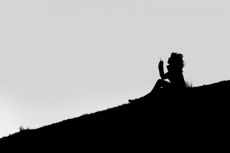 A Silhouette of a girl seated on the ground, smoking