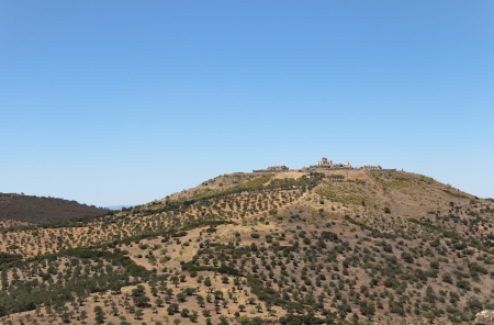 A Fortress in the top of one mountain with many trees Editorial