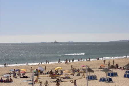 A beach full of people in the middle of the summer