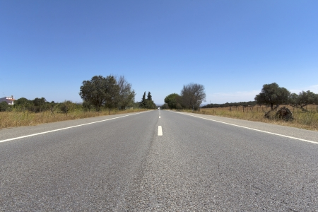 A lonely road in the middle of a field centered on frame Stock Photo
